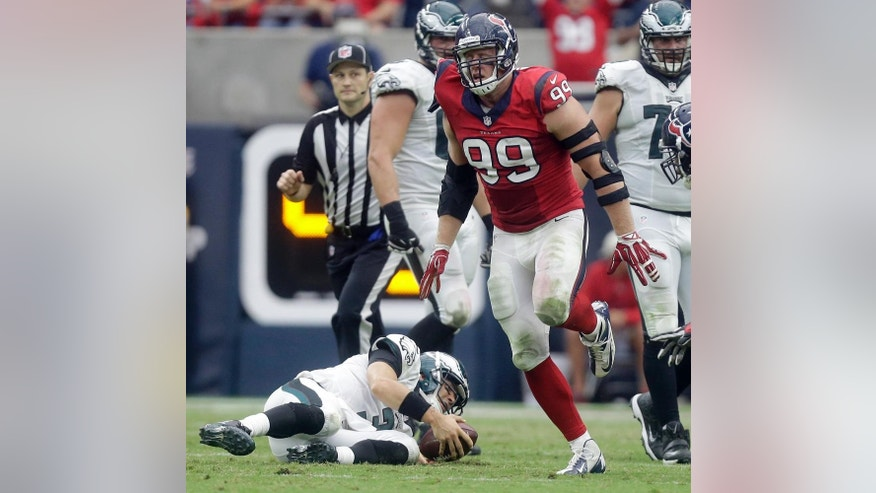 Philadelphia Eagles quarterback Mark Sanchez, left, slowly gets up after being sacked 7-yard loss by Houston Texans defensive end J.J. Watt, right, during the second quarter of an NFL football game, Sunday, Nov. 2, 2014, in Houston. (AP Photo/Patric Schneider)