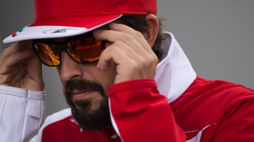 Ferrari driver Fernando Alonso of Spain puts on his sunglasses as he walks on the paddock of the Interlagos circuit in Sao Paulo, Brazil, Thursday, Nov. 6, 2014.  Formula One teams are in Sao Paulo to compete in the 2014 Brazilian Grand Prix, Sunday. (AP Photo/Felipe Dana)