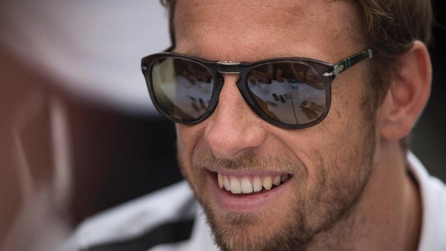 McLaren driver Jenson Button of Britain talks to reporters on the paddock of the Interlagos circuit in Sao Paulo, Brazil, Thursday, Nov. 6, 2014.  Formula One teams are in Sao Paulo to compete in the 2014 Brazilian Grand Prix, Sunday. (AP Photo/Felipe Dana)