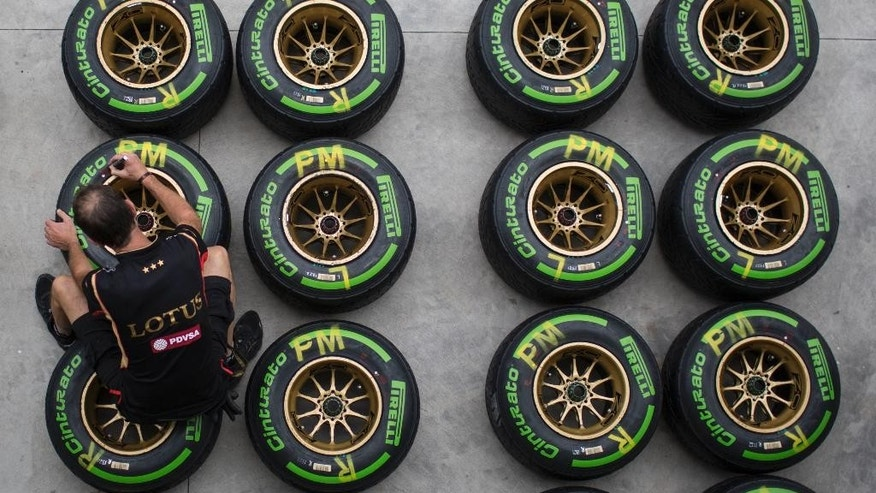 A Lotus crew member marks a tire, in the boxes of the Interlagos circuit in Sao Paulo, Brazil, Thursday, Nov. 6, 2014. Formula One teams are in Sao Paulo to compete in the 2014 Brazilian Grand Prix, Sunday. (AP Photo/Felipe Dana)