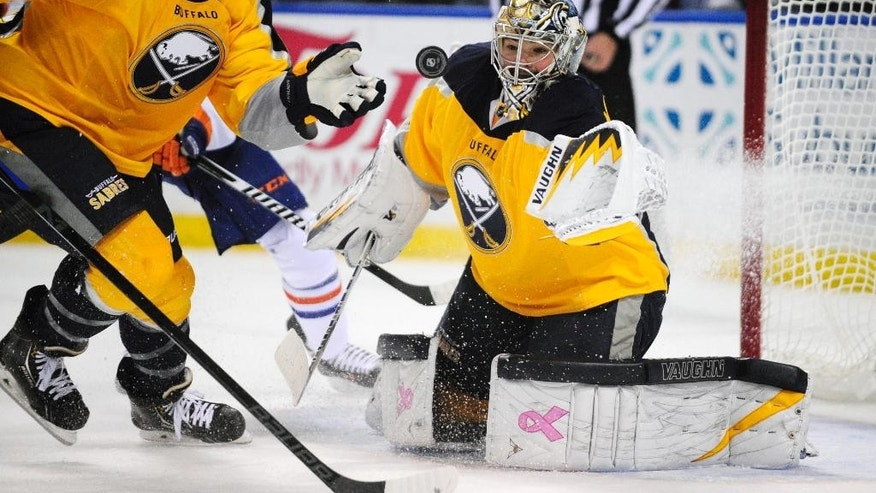 Buffalo Sabres left winger Nicolas Deslauriers (44) and goaltender Michal Neuvirth (34) eye the puck during the second period of an NHL hockey game against the Edmonton Oilers Friday, Nov. 7, 2014, in Buffalo, N.Y. (AP Photo/Gary Wiepert)