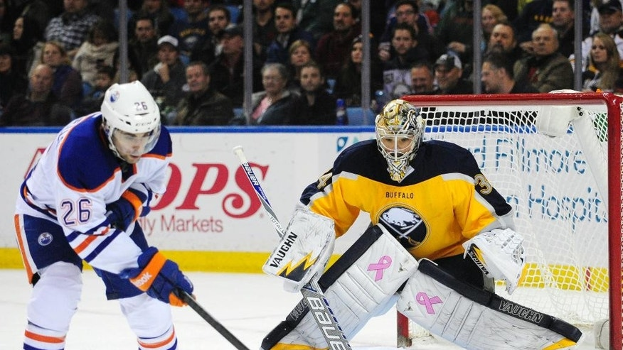 Edmonton Oilers center Mark Arcobello (26) tries to deflect the puck against Buffalo Sabres goaltender Michal Neuvirth (34), of the Czech Republic, during the second period of an NHL hockey game Friday, Nov. 7, 2014, in Buffalo, N.Y. (AP Photo/Gary Wiepert)