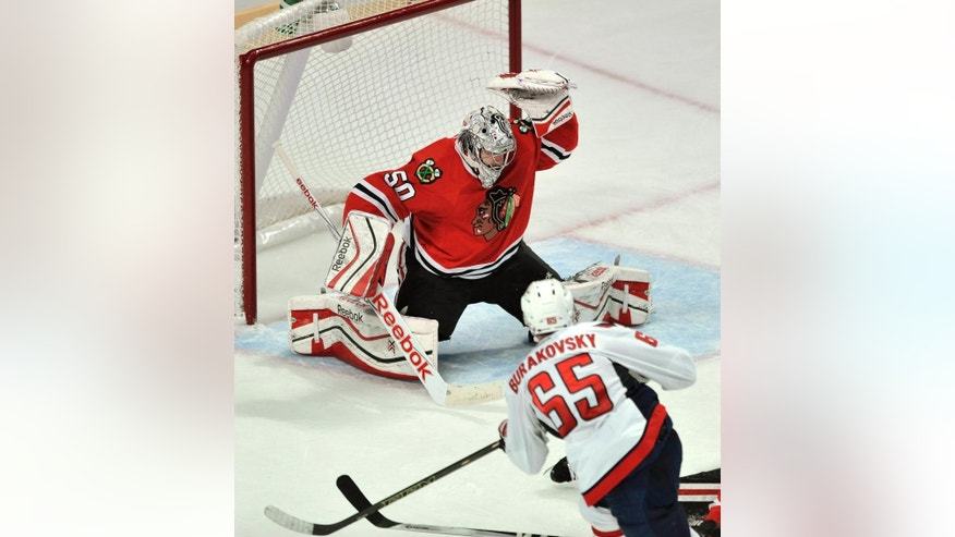 Washington Capitals' Andre Burakovsky (65), of Austria, scores a goal against Chicago Blackhawks goalie Corey Crawford during the second period of an NHL hockey game in Chicago, Friday, Nov. 7, 2014.  (AP Photo/Paul Beaty)