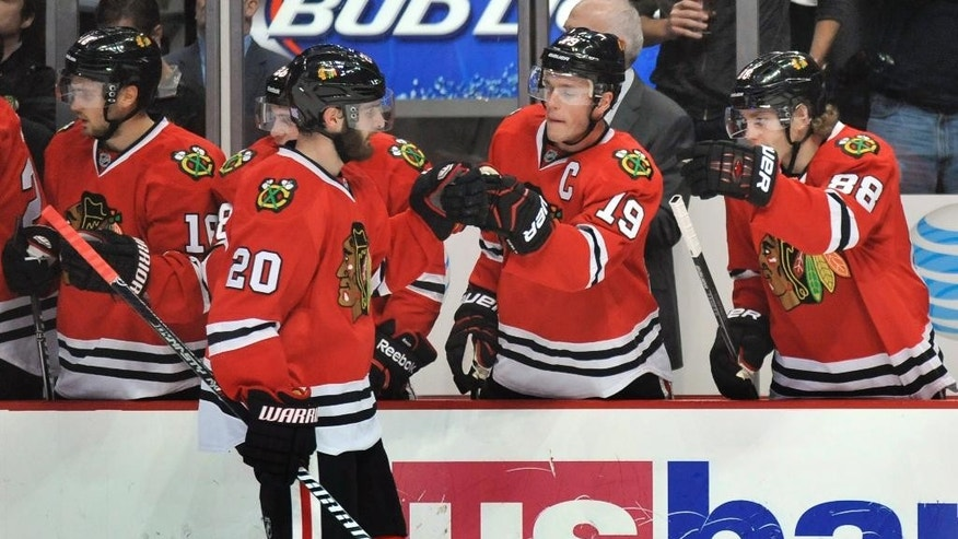 Chicago Blackhawks' Brandon Saad (20) celebrates with teammates Jonathan Toews (19) and Patrick Kane (88) on the bench after scoring a goal during the first period of an NHL hockey game against the Washington Capitals in Chicago, Friday, Nov. 7, 2014. (AP Photo/Paul Beaty)