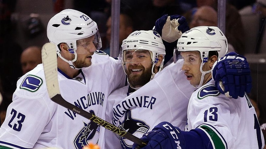 From left, Vancouver Canucks' Alexander Edler and Chris Higgins celebrate a goal made by Nick Bonino (13) during the second period of an NHL hockey game against the San Jose Sharks on Thursday, Nov. 6, 2014, in San Jose, Calif. (AP Photo/Ben Margot)