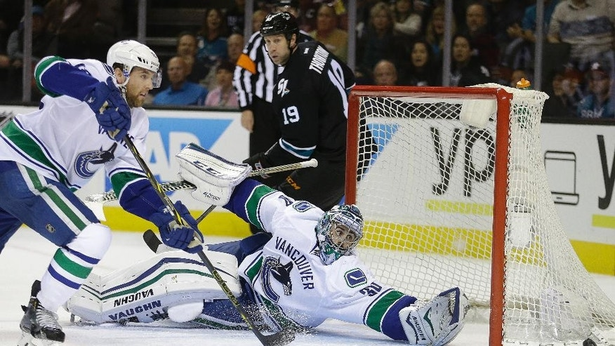 Vancouver Canucks goalie Ryan Miller (30) deflects a shot during the first period of an NHL hockey game against the San Jose Sharks, Thursday, Nov. 6, 2014, in San Jose, Calif. (AP Photo/Ben Margot)