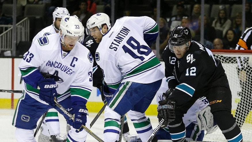 Vancouver Canucks' Henrik Sedin, left, Ryan Stanton (18) and San Jose Sharks' Patrick Marleau, right, fight for the puck during the first period of an NHL hockey game Thursday, Nov. 6, 2014, in San Jose, Calif. (AP Photo/Ben Margot)