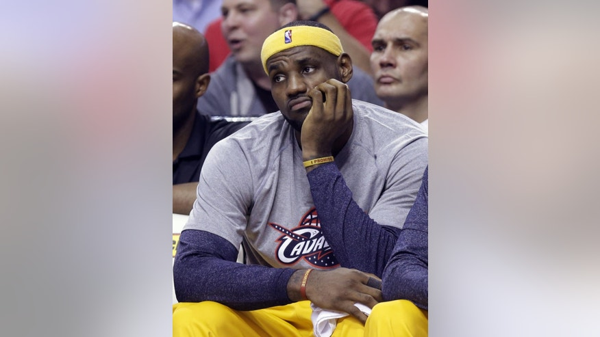 Cleveland Cavaliers forward LeBron James watches from the bench during the second half of the Cavaliers' NBA basketball game against the Portland Trail Blazers in Portland, Ore., Tuesday, Nov. 4, 2014. James scored 11 points. The Trail Blazers won 101-82. (AP Photo/Don Ryan)
