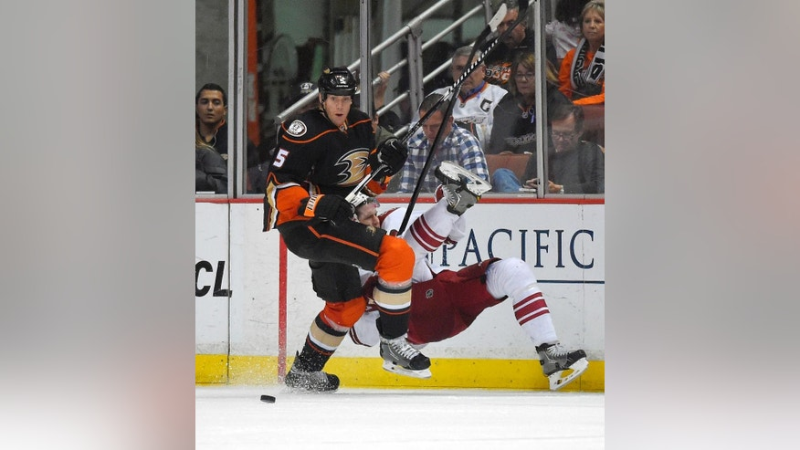 Anaheim Ducks defenseman Bryan Allen, left, puts Arizona Coyotes defenseman Oliver Ekman-Larsson, of Sweden, into the boards during the second period of an NHL hockey game, Friday, Nov. 7, 2014, in Anaheim, Calif.  (AP Photo/Mark J. Terrill)