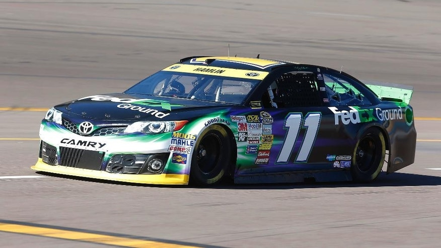 Denny Hamlin practices for the NASCAR Sprint Cup series auto race at Phoenix International Raceway in Avondale, Ariz., Friday, Nov. 7, 2014. (AP Photo/Rick Scuteri)