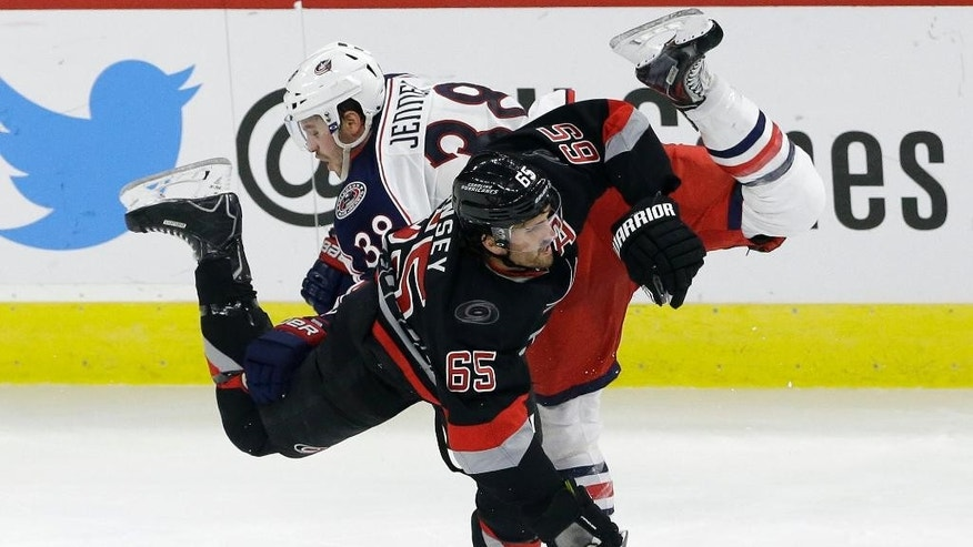 Carolina Hurricanes' Ron Hainsey (65) and Columbus Blue Jackets' Boone Jenner (38) collide during the third period of an NHL hockey game in Raleigh, N.C., Friday, Nov. 7, 2014. Carolina won 3-2 in overtime. (AP Photo/Gerry Broome)