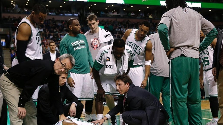 Boston Celtics guard Marcus Smart lies on the floor after injuring his left leg during the second half of an NBA basketball game against the Indiana Pacers in Boston, Friday, Nov. 7, 2014. Smart was taken from the court on a stretcher. The Celtics defeated the Pacers 101-98. (AP Photo/Charles Krupa)