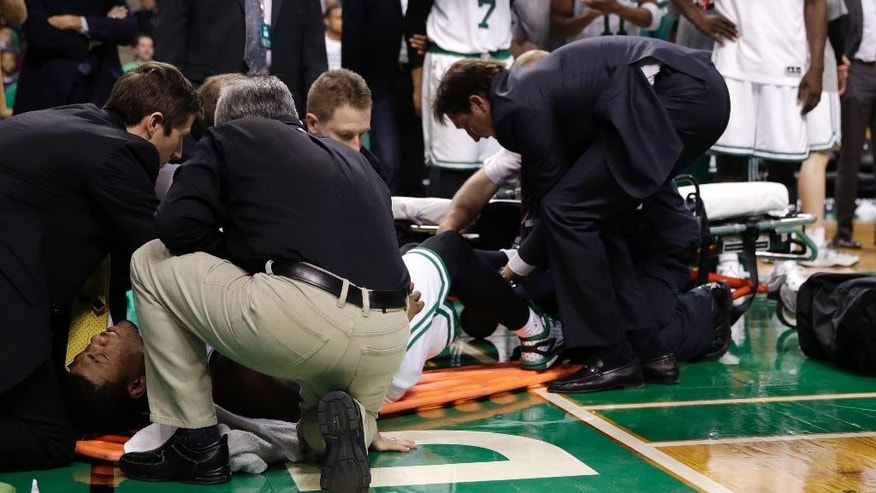Boston Celtics guard Marcus Smart is loaded onto a backboard after injuring his left leg during the second half of an NBA basketball game against the Indiana Pacers in Boston, Friday, Nov. 7, 2014. The Celtics defeated the Pacers 101-98. (AP Photo/Charles Krupa)