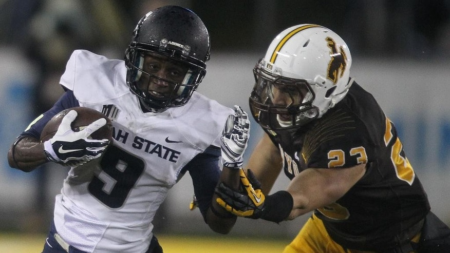 Utah State's Jojo Natson (9) runs the ball against Wyoming's Tim Kamana during an NCAA college football game Friday, Nov. 7, 2014, in Laramie, Wyo. (AP Photo/Wyoming Tribune Eagle, Miranda Grubbs)