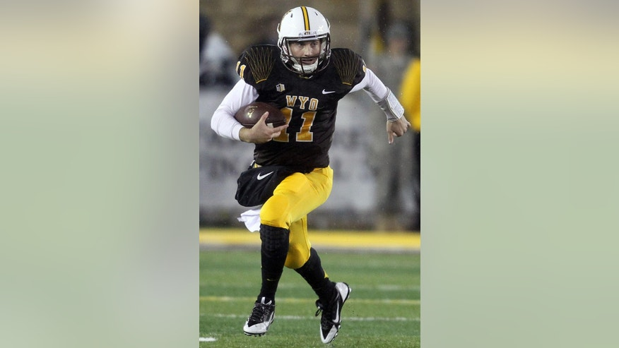 Wyoming quarterback Colby Kirkegaard runs the ball against Utah State during an NCAA college football game Friday, Nov. 7, 2014, in Laramie, Wyo. (AP Photo/Wyoming Tribune Eagle, Miranda Grubbs)