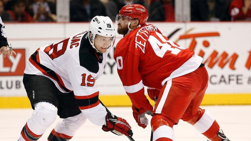 New Jersey Devils center Travis Zajac (19) and Detroit Red Wings left wing Henrik Zetterberg (40) battle for the puck in the second period of an NHL hockey game in Detroit, Friday, Nov. 7, 2014. (AP Photo/Paul Sancya)