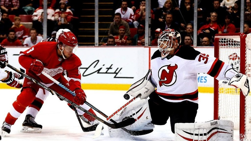 New Jersey Devils goalie Cory Schneider (35) stops a Detroit Red Wings left wing Justin Abdelkader (8) shot in the first period of an NHL hockey game in Detroit, Friday, Nov. 7, 2014. (AP Photo/Paul Sancya)