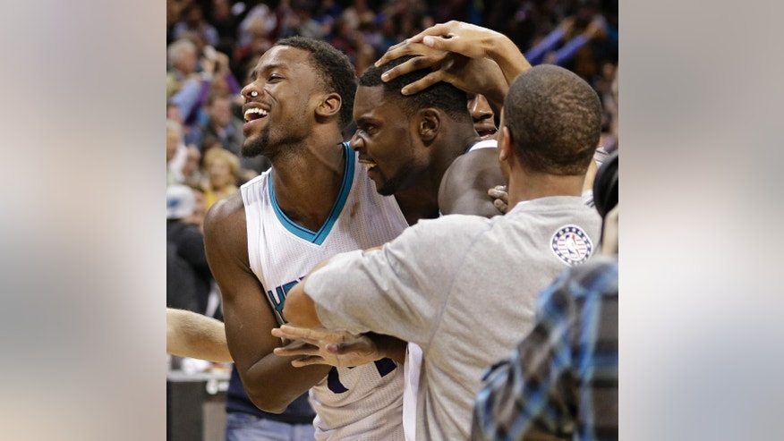 Charlotte Hornets' Lance Stephenson, center, is congratulated by teammates Michael Kidd-Gilchrist, left, and Jannero Pargo, right, after his game-winning basket against the Atlanta Hawks in an NBA basketball game in Charlotte, N.C., Friday, Nov. 7, 2014. The Hornets won 122-119 in double overtime. (AP Photo/Chuck Burton)