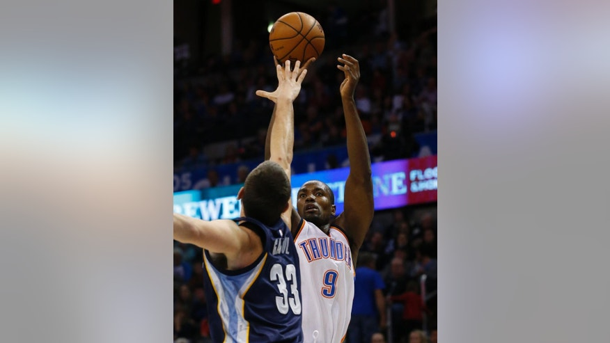 Oklahoma City Thunder forward Serge Ibaka (9) shoots over Memphis Grizzlies center Marc Gasol (33) during the first quarter of an NBA basketball game in Oklahoma City, Friday, Nov. 7, 2014. (AP Photo/Sue Ogrocki)
