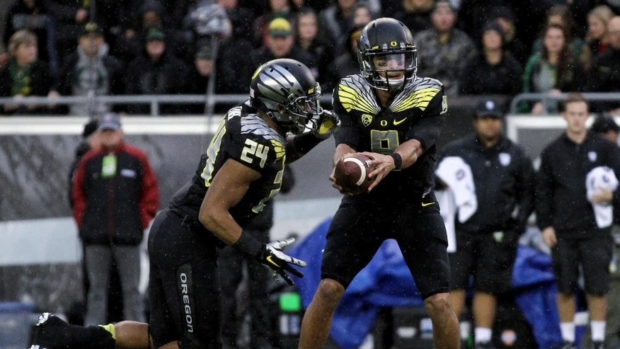 FILE - In this Nov. 1, 2014, file photo, Oregon quarterback Marcus Mariota (8) hands the ball to running back Thomas Tyner (24) during the first quarter against Stanford in an NCAA college football game in Eugene, Ore. Mariota is the highest-rated passer in country (187.21). He is tied for third in touchdown passes with 26 and has thrown just two interceptions. (AP Photo/Ryan Kang, File)