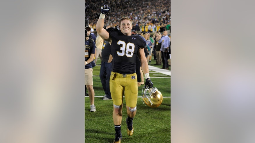 FILE - In this Saturday Sept. 9, 2014 file photo, Notre Dame linebacker Joe Schmidt reacts after the  victory over Michigan in an NCAA college football game in South Bend, Ind. Coach Brian Kelly isn't sure how eighth-ranked Notre Dame will replace the leadership of middle linebacker Joe Schmidt. The senior, who sustained a season-ending fractured and dislocated left ankle in a 49-39 victory over Navy on Saturday, had been making sure the Fighting Irish were in the right defense and lined up correctly.  (AP Photo/Joe Raymond, File)