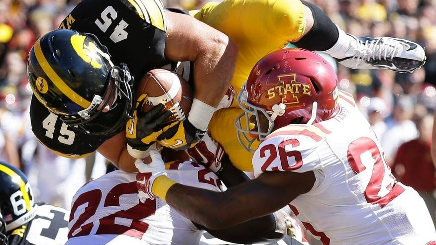 FILE - In this Sept. 13, 2014, file photo, Iowa running back Mark Weisman (45) scores on a 1-yard touchdown run over Iowa State defensive backs T.J. Mutcherson (22) and Qujuan Floyd (26) during the first half of an NCAA college football game in Iowa City, Iowa. Iowa renews a rivalry against Minnesota on Saturday, Nov. 8, with the Gophers trying to regain possession of that prized bronze pig trophy. (AP Photo/Charlie Neibergall, File)