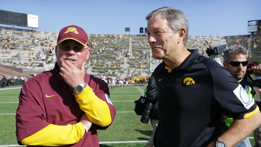 FILE - In this Sept. 29, 2012, file photo, Minnesota coach Jerry Kill, left, talks with Iowa coach Kirk Ferentz before an NCAA college football game in Iowa City, Iowa. As the Iowa-Minnesota rivalry is renewed, with the Gophers trying to regain possession of that prized bronze pig after two straight wins in the series by the Hawkeyes, this game is for more than just the Floyd of Rosedale trophy. It's one of several head-to-head matchups this month that will shape the Big Ten West race. (AP Photo/Charlie Neibergall, File)