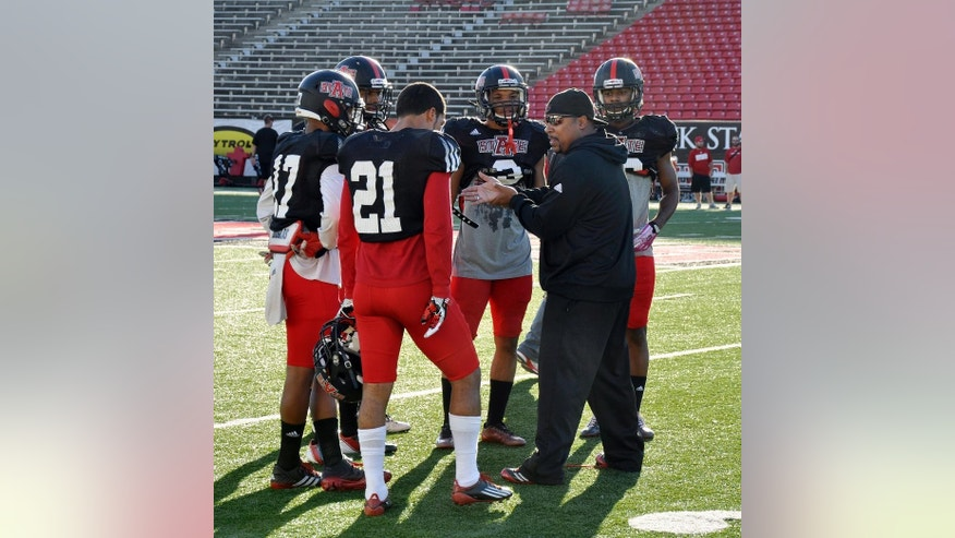 FILE - In this Oct. 17, 2014, file photo, Arkansas State assistant coach Trooper Taylor talks with senior Andrew Tryon (No. 21) and a group of players during a practice in Jonesboro, Ark. Even after being investigated for possible recruiting violations while at Auburn, Taylor _ one of the top recruiters in the country _ has remained as outgoing and confident as ever at his new home, Arkansas State. (AP Photo/Kurt Voigt, File)