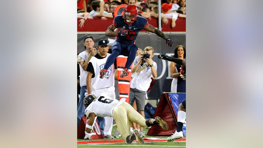 Arizona running back Samajie Grant (10) leaps over Colorado defensive back Evan White (6) during the first half of an NCAA college football game, Saturday, Nov. 8, 2014, in Tucson, Ariz. (AP Photo/Rick Scuteri)