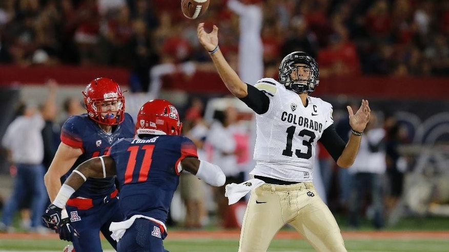 Arizona safety William Parks (11) pressures Colorado quarterback Sefo Liufau (13) during the first half of an NCAA college football game, Saturday, Nov. 8, 2014, in Tucson, Ariz. (AP Photo/Rick Scuteri)