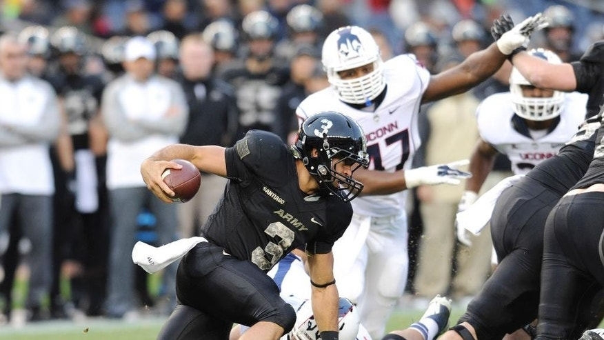 Army quarterback Angel Santiago (3) runs with the ball during the first half of an NCAA college football game against Connecticut Saturday, Nov. 8, 2014, at Yankee Stadium in New York. (AP Photo/Bill Kostroun)