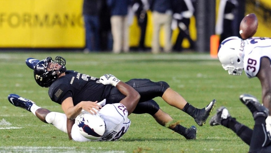 Army quarterback Angel Santiago (3) fumbles the ball as he is tackled by Comnnecticut linebacker Jefferson Ashiru (32) during the first half of an NCAA college football game against Connecticut Saturday, Nov. 8, 2014, at Yankee Stadium in New York. (AP Photo/Bill Kostroun)