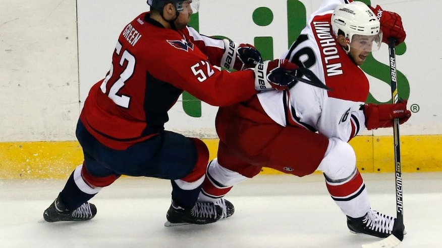 Washington Capitals defenseman Mike Green (52) defends against Carolina Hurricanes center Elias Lindholm (16), from Sweden, in the overtime period of an NHL hockey game, Saturday, Nov. 8, 2014, in Washington. The Capitals won 4-3. (AP Photo/Alex Brandon)