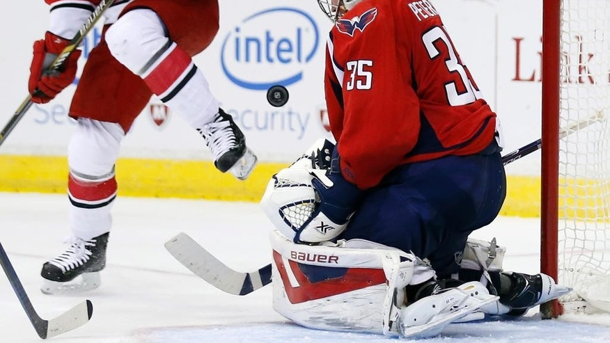 Carolina Hurricanes center Elias Lindholm (16), from Sweden, watches as the puck bounces off Washington Capitals goalie Justin Peters (35) in the second period of an NHL hockey game, Saturday, Nov. 8, 2014, in Washington. (AP Photo/Alex Brandon)