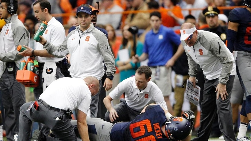 Syracuse's Sean Hickey is helped by trainers after getting injured on a play in the second quarter of an NCAA college football game against Duke in Syracuse, N.Y., Saturday, Nov. 8, 2014. Syracuse's head coach Scott Shafer, right, looks on. (AP Photo/Nick Lisi)