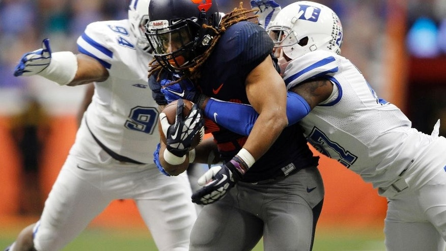 Syracuse's Tyson Prince-Gully, center, is taken down by Duke's Jordan DeWalt-Ondijo, left, and DeVon Edwards, right, in the first half of an NCAA college football game in Syracuse, N.Y., Saturday, Nov. 8, 2014. (AP Photo/Nick Lisi)