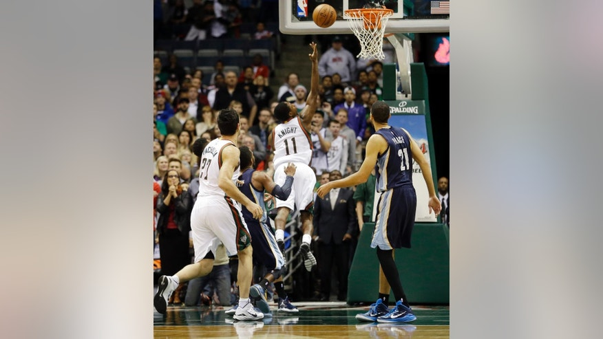 Milwaukee Bucks' Brandon Knight (11) is fouled as he puts up a shot in the final seconds of the second half of an NBA basketball game against the Memphis Grizzlies Saturday, Nov. 8, 2014, in Milwaukee. The Bucks won 93-92. (AP Photo/Morry Gash)