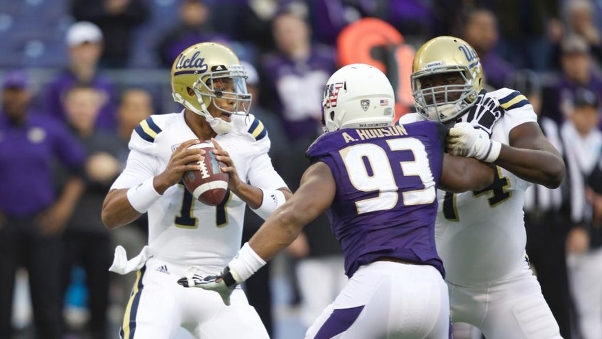 UCLA quarterback Brett Hundley, left, looks to pass as he avoids the rush of Washington defensive lineman Andrew Hudson in the first half of an NCAA college football game Saturday, Nov. 8, 2014, in Seattle. (AP Photo/Stephen Brashear)
