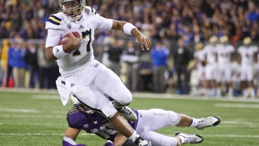 UCLA quarterback Brett Hundley runs with the ball in the second half of an NCAA college football game against Washington, Saturday, Nov. 8, 2014, in Seattle. UCLA won the game 44-30. (AP Photo/Stephen Brashear)