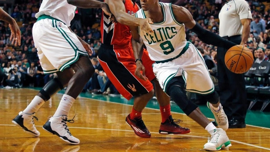 Boston Celtics guard Rajon Rondo (9) drives past Toronto Raptors guard Kyle Lowry, middle, during the first quarter of an NBA basketball game in Boston, Wednesday, Nov. 5, 2014. (AP Photo/Elise Amendola)