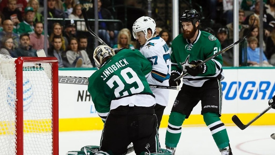 Dallas Stars' Anders Lindback (29), of Sweden, attempts to reach the puck at his knees under pressure from San Jose Sharks' Tommy Wingels (57) as Stars' Jordie Benn (24) watches during the second period of an NHL hockey game, Saturday, Nov. 8, 2014, in Dallas. (AP Photo/Tony Gutierrez)
