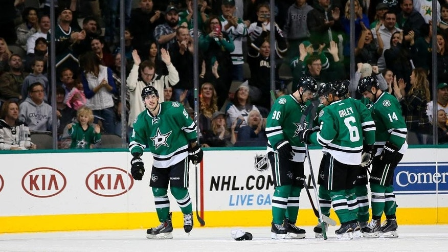 Fans cheer as Dallas Stars' Tyler Seguin (91) skates back to the bench after celebrating his goal against the San Jose Sharks with Jason Spezza (90), Trevor Daley (6), Jamie Benn (14) and the rest of his line in the second period of an NHL hockey game, Saturday, Nov. 8, 2014, in Dallas. The goal was Seguin's third of the game. (AP Photo/Tony Gutierrez)