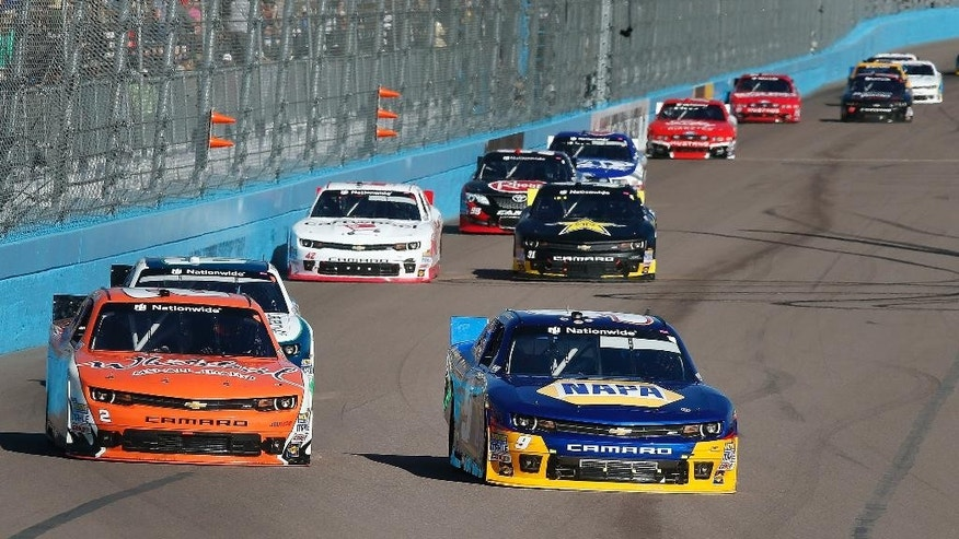 Chase Elliott, right, leads Brian Scott into the first turn during a NASCAR Nationwide Series auto race at Phoenix International Raceway, Saturday, Nov. 8, 2014, in Avondale, Ariz. (AP Photo/Ross D. Franklin)
