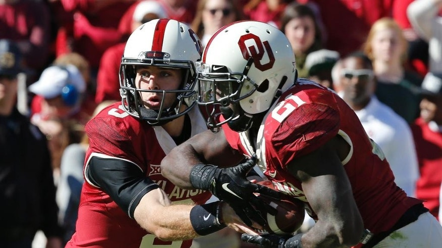 Oklahoma quarterback Trevor Knight (9) hands off to Keith Ford (21) in the second quarter of an NCAA college football game against Baylor in Norman, Okla., Saturday, Nov. 8, 2014. (AP Photo/Sue Ogrocki)