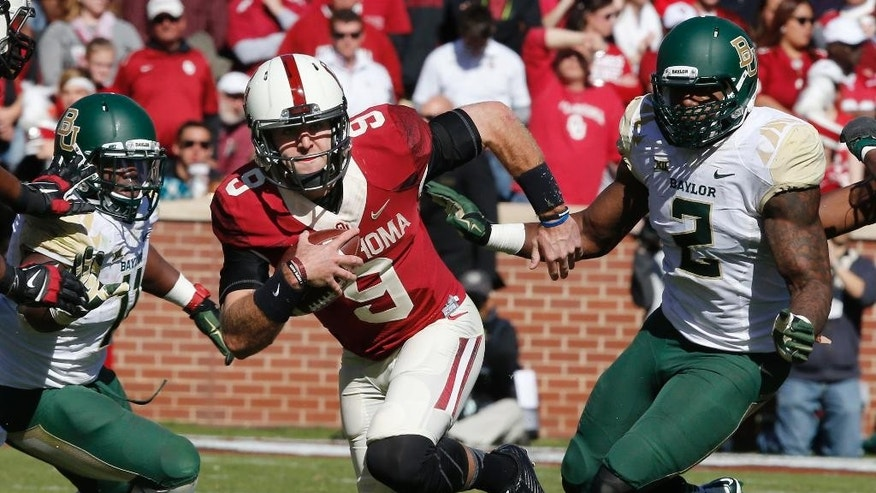 Oklahoma quarterback Trevor Knight (9) scrambles under pressure from Baylor linebacker Taylor Young (11) and defensive end Shawn Oakman (2) in the second quarter of an NCAA college football game in Norman, Okla., Saturday, Nov. 8, 2014. (AP Photo/Sue Ogrocki)