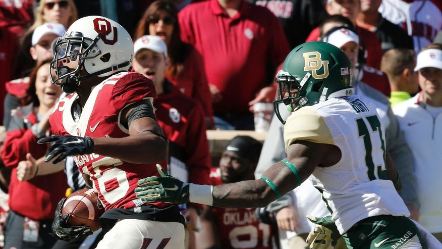 Oklahoma wide receiver Michiah Quick (16) carries in front of Baylor safety Terrell Burt (13) in the second quarter of an NCAA college football game in Norman, Okla., Saturday, Nov. 8, 2014. (AP Photo/Sue Ogrocki)