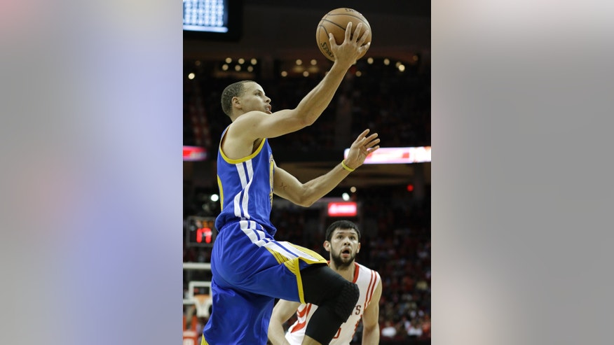 Houston Rockets' Kostas Papanikolaou, right, watches as Golden State Warriors' Stephen Curry, left, goes to the basket in the first half of an NBA basketball game Saturday, Nov. 8, 2014, in Houston. The Warriors won 98-89. (AP Photo/Pat Sullivan)