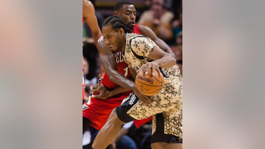 New Orleans Pelicans guard Tyreke Evans guards San Antonio Spurs forward Kawhi Leonard in the first half of an NBA basketball game in San Antonio on Saturday, Nov. 8, 2014. (AP Photo/Bahram Mark Sobhani)