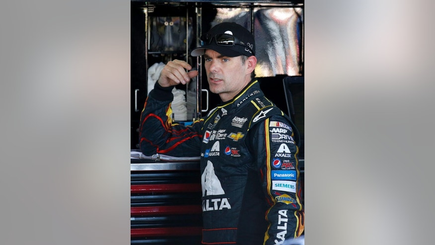 Jeff Gordon talks to crew members in the garage area during a NASCAR Sprint Cup Series auto race practice session at Phoenix International Raceway, Saturday, Nov. 8, 2014, in Avondale, Ariz. (AP Photo/Ross D. Franklin)