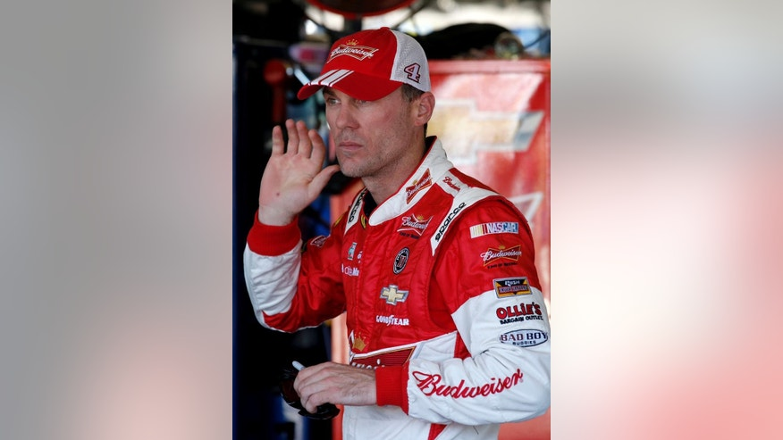 Kevin Harvick tries to hear something from a crew member in the garage area during a NASCAR Sprint Cup Series auto race practice session at Phoenix International Raceway Saturday, Nov. 8, 2014, in Avondale, Ariz. (AP Photo/Ross D. Franklin)